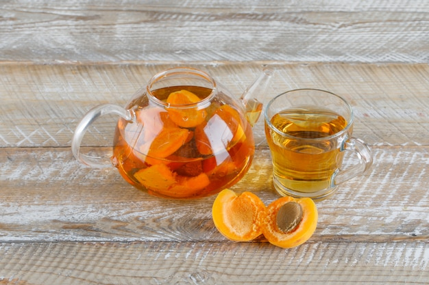 Apricot tea in teapot and glass mug with apricots top view on a wooden table