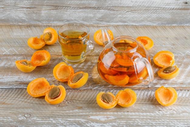 Tè all'albicocca in tazza teiera e vetro con vista dall'alto di albicocche su un tavolo di legno