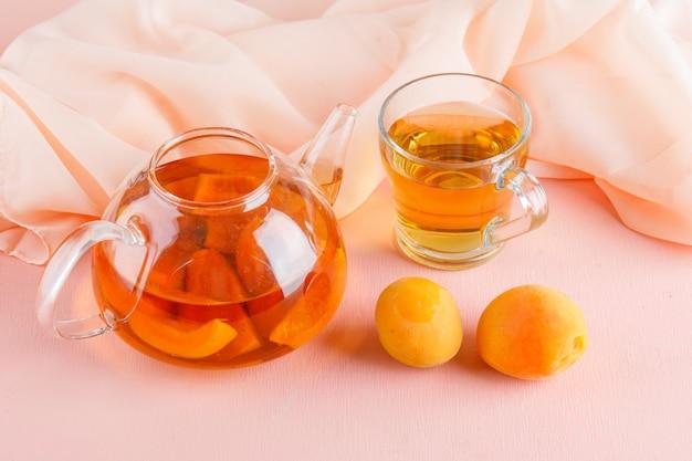 Tè all'albicocca con albicocche in teiera e tazza, vista dall'alto.