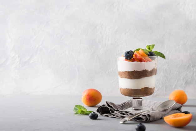 Apricot trifle, chocolate biscuit, layered dessert with  berry and  cream cheese on grey.