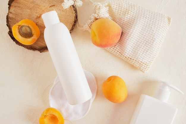 크림이나 비누를 위한 살구와 플라스틱 흰색 병 모형, 나무로 만든 톱 컷의 나무 연단