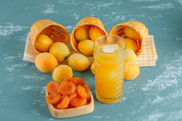 Apricots in baskets with juice, dried apricots top view on plaster and picnic cloth