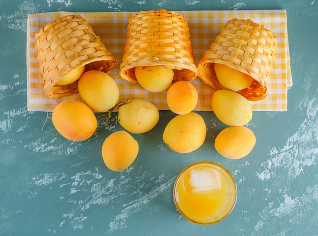 Apricots in baskets with juice flat lay on plaster and picnic cloth
