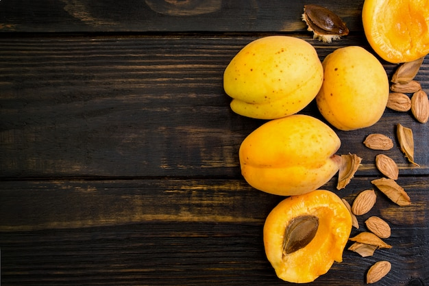Apricots in a clay plate on a wooden table with broken bones.  top view