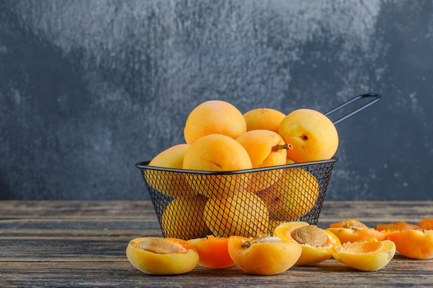 Apricots in a colander on wooden and plaster wall. side view.