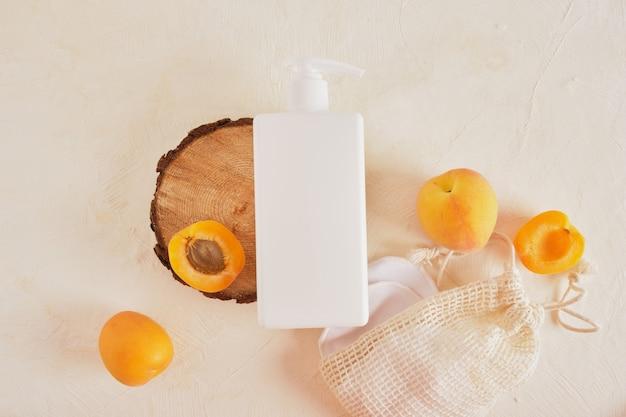 アプリコットプラスチック製の白いボトル、クリームまたは石鹸用ディスペンサー、木から切り取ったのこぎりからの木製の表彰台
