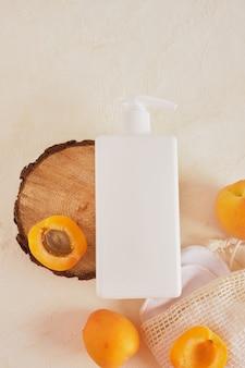 アプリコットプラスチック製の白いモックアップボトル、クリームまたは石鹸用ディスペンサー、明るい背景の上面図で木から切り取ったのこぎりからの木製の表彰台