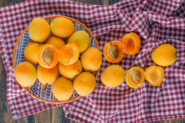 Apricots in a plate flat lay on picnic cloth and wooden table