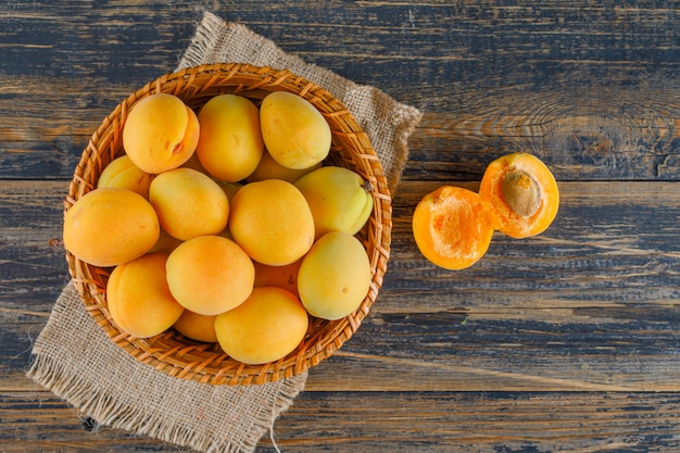 Apricots in a wicker basket on wooden and piece of sack. flat lay.