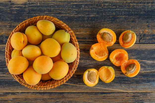 Apricots in a wicker basket on wooden table, flat lay.