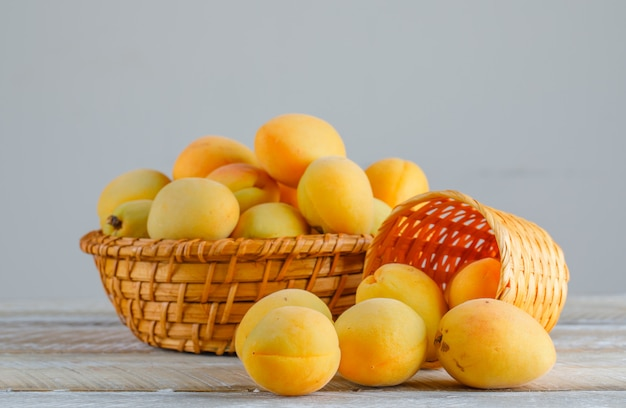 Apricots in wicker baskets on wooden table. side view.