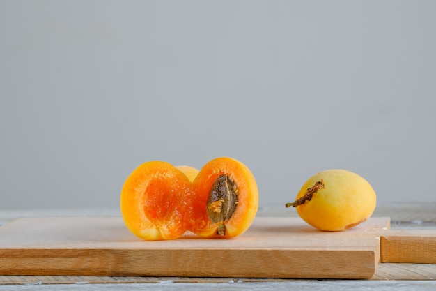Apricots with cutting board on wooden table, side view.