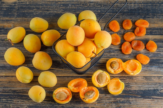 Apricots with dried apricots in a colander on wooden table, top view.