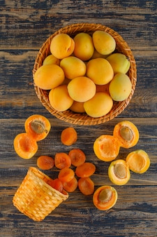 Apricots with dried apricots in a wicker basket on wooden table, top view.