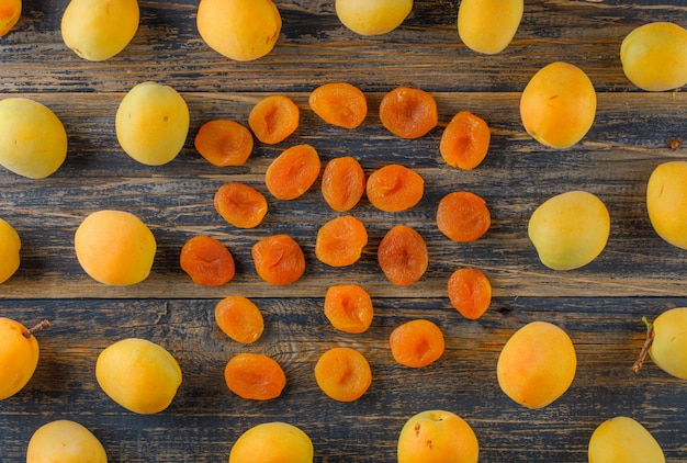 Apricots with dried apricots on wooden table, flat lay.