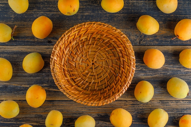 Apricots with empty basket on wooden table, flat lay.
