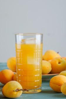 Albicocche con succo in un piatto, vista laterale.