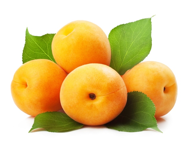 Apricots with leaves on a white surface