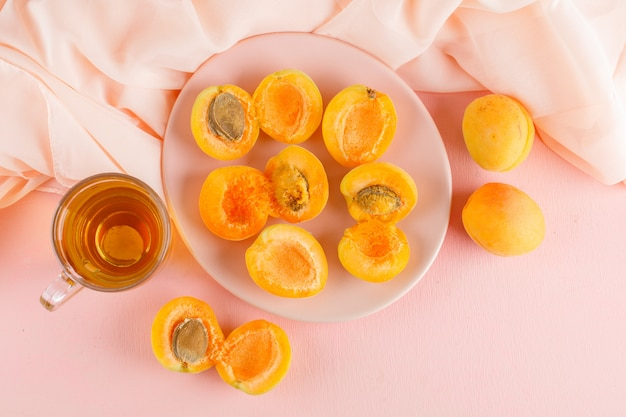 Apricots with tea in a plate, flat lay.