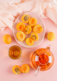 Apricots with tea in a plate, top view.