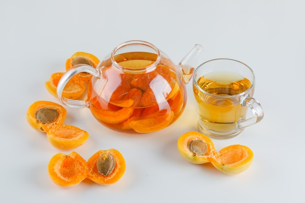 Apricots with tea on white table, top view.