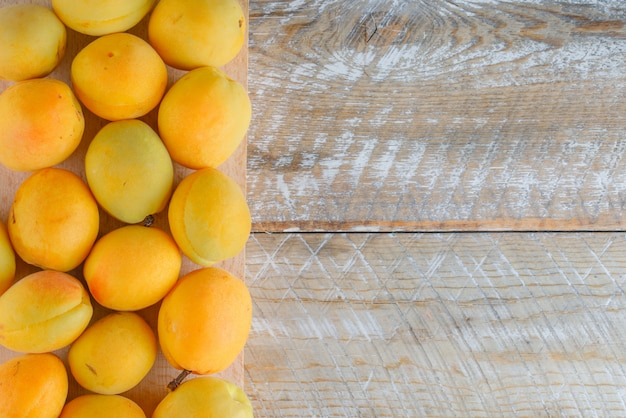 Apricots on wooden and cutting board, flat lay.