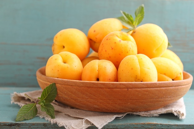 Apricots in a wooden plate with mint leaves