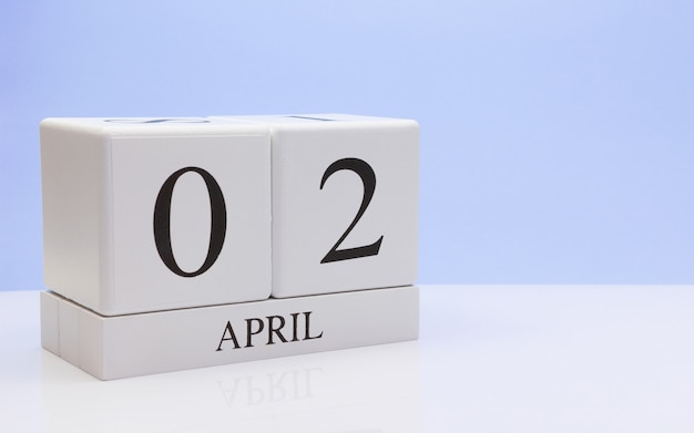 April 02st. day 02 of month, daily calendar on white table with reflection