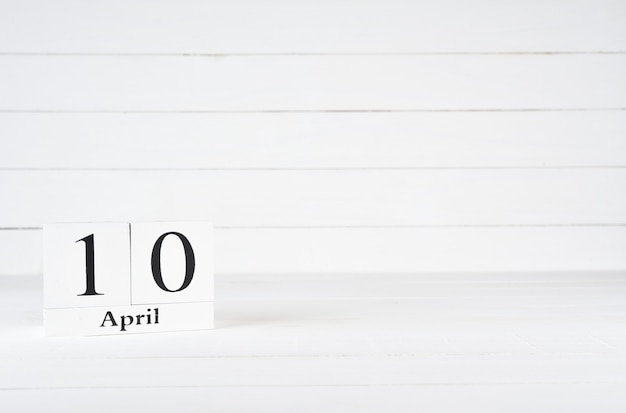 April 10th, day 10 of month, birthday, anniversary, wooden block calendar on white wooden background with copy space for text.