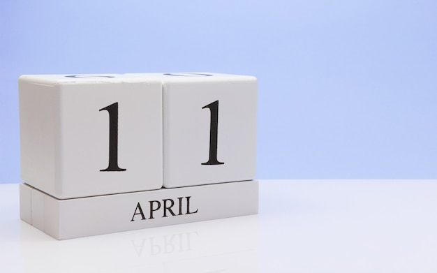April 11st. day 11 of month, daily calendar on white table with reflection