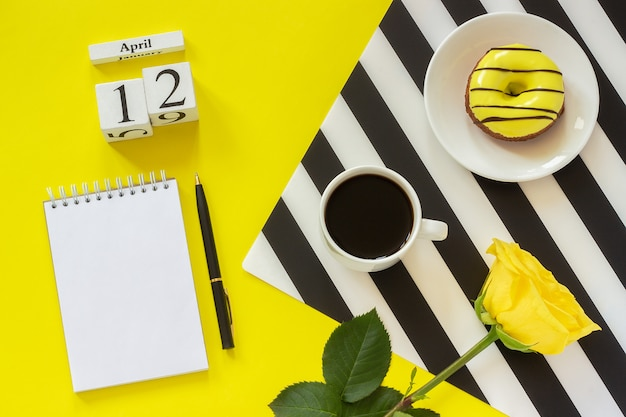 April 12. cup of coffee donut rose notepad on yellow background. concept stylish workplace