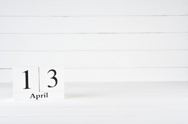 April 13th, day 13 of month, birthday, anniversary, wooden block calendar on white wooden background with copy space for text.