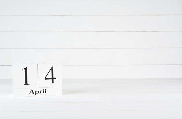 April 14th, day 14 of month, birthday, anniversary, wooden block calendar on white wooden background with copy space for text.
