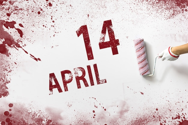 April 14th. day 14 of month, calendar date. the hand holds a roller with red paint and writes a calendar date on a white background. spring month, day of the year concept.