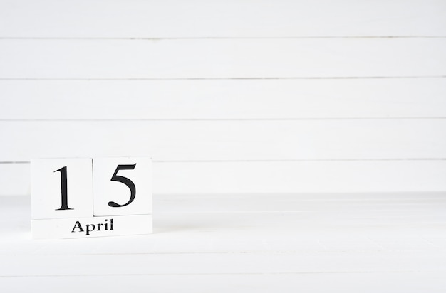 April 15th, day 15 of month, birthday, anniversary, wooden block calendar on white wooden background with copy space for text.