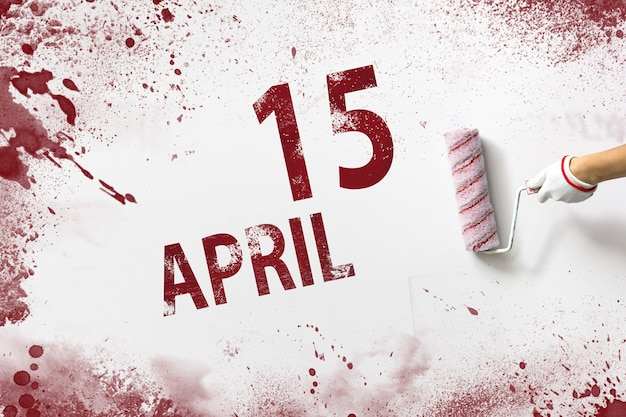 April 15th. day 15 of month, calendar date. the hand holds a roller with red paint and writes a calendar date on a white background. spring month, day of the year concept.