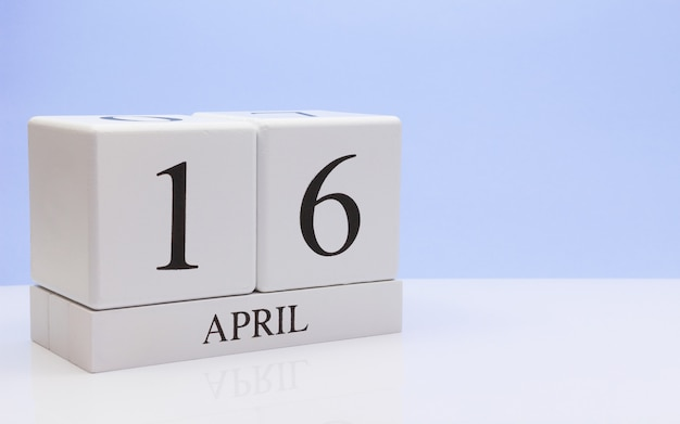 April 16st. day 16 of month, daily calendar on white table with reflection