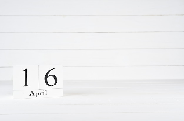 April 16th, day 16 of month, birthday, anniversary, wooden block calendar on white wooden background with copy space for text.