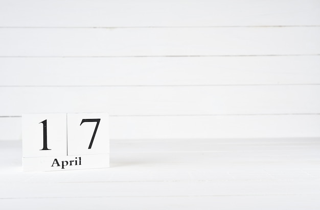 April 17th, day 17 of month, birthday, anniversary, wooden block calendar on white wooden background with copy space for text.