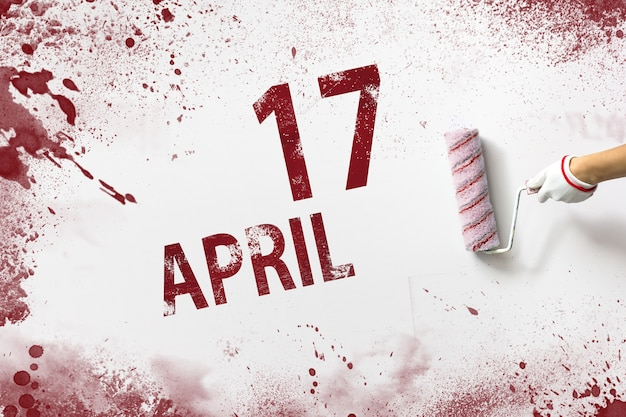 April 17th. day 17 of month, calendar date. the hand holds a roller with red paint and writes a calendar date on a white background. spring month, day of the year concept.