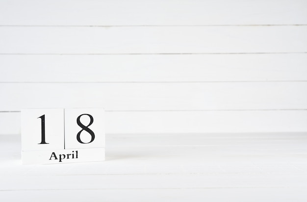 April 18th, day 18 of month, birthday, anniversary, wooden block calendar on white wooden background with copy space for text.