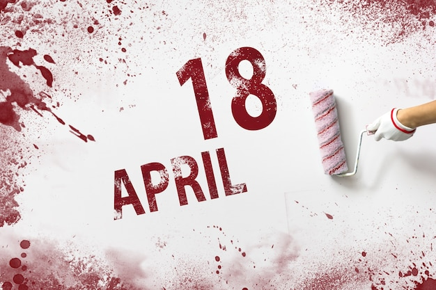 April 18th. day 18 of month, calendar date. the hand holds a roller with red paint and writes a calendar date on a white background. spring month, day of the year concept.