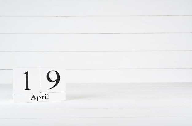 April 19th, day 19 of month, birthday, anniversary, wooden block calendar on white wooden background with copy space for text.