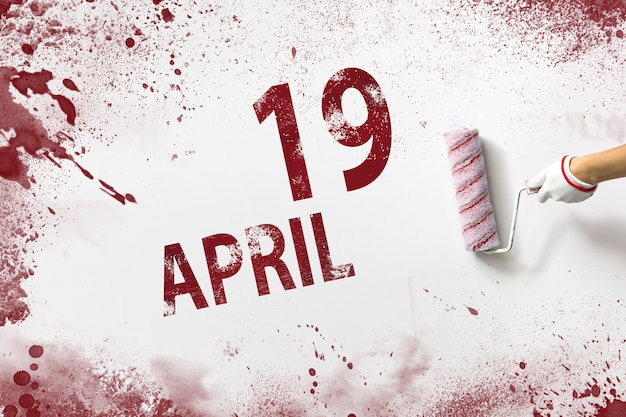 April 19th. day 19 of month, calendar date. the hand holds a roller with red paint and writes a calendar date on a white background. spring month, day of the year concept.