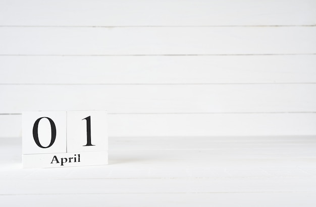 April 1st, day 1 of month, birthday, anniversary, wooden block calendar on white wooden background with copy space for text.