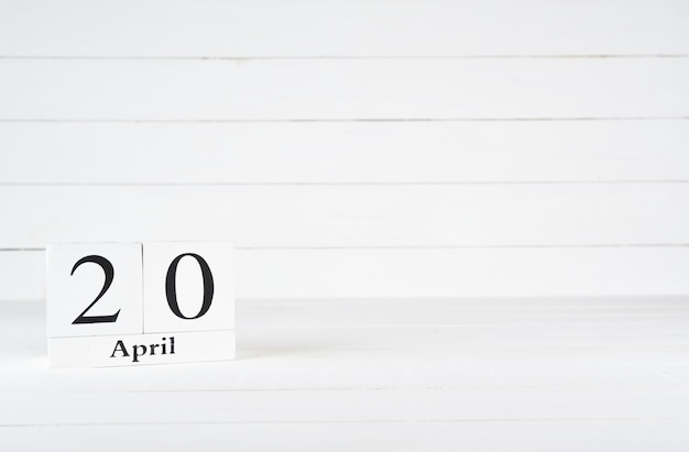 April 20th, day 20 of month, birthday, anniversary, wooden block calendar on white wooden background with copy space for text.