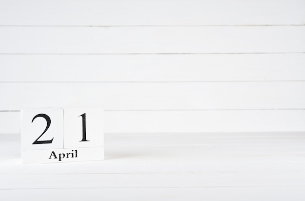 April 21st, day 21 of month, birthday, anniversary, wooden block calendar on white wooden background with copy space for text.