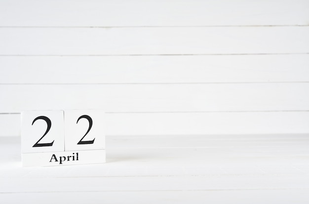 April 22nd, day 22 of month, birthday, anniversary, wooden block calendar on white wooden background with copy space for text.