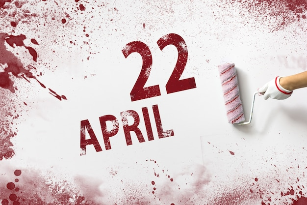 April 22nd. day 22 of month, calendar date. the hand holds a roller with red paint and writes a calendar date on a white background. spring month, day of the year concept.