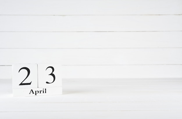 April 23rd, day 23 of month, birthday, anniversary, wooden block calendar on white wooden background with copy space for text.